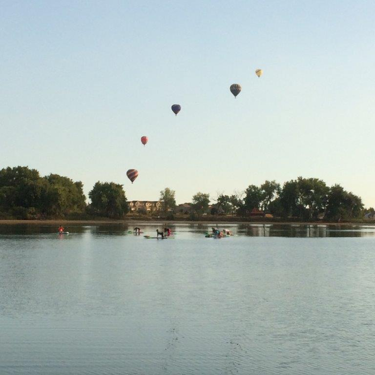 Stand Up Paddleboarders with Hot Air Balloons in Background