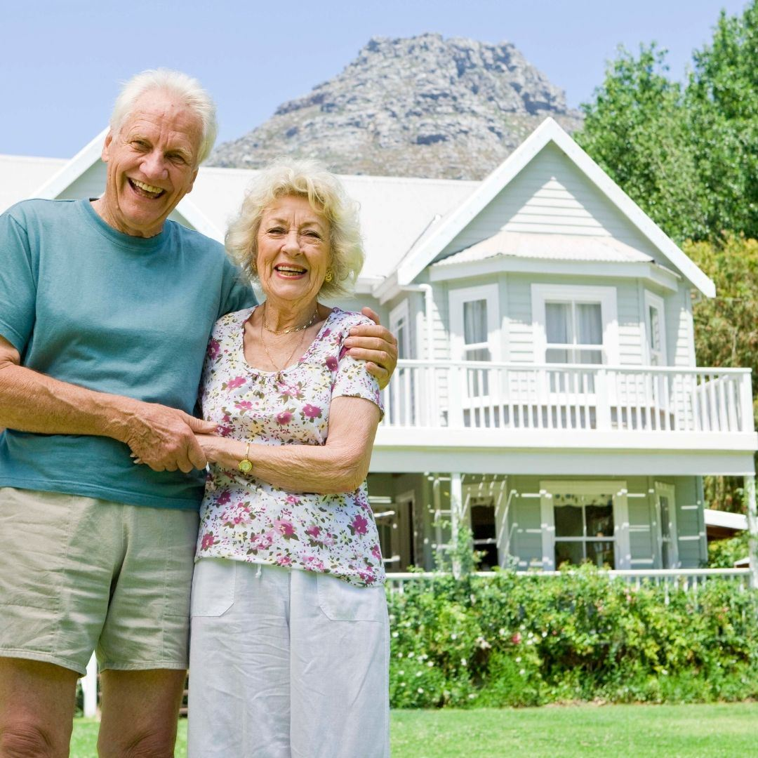 Image of senior couple in front of home