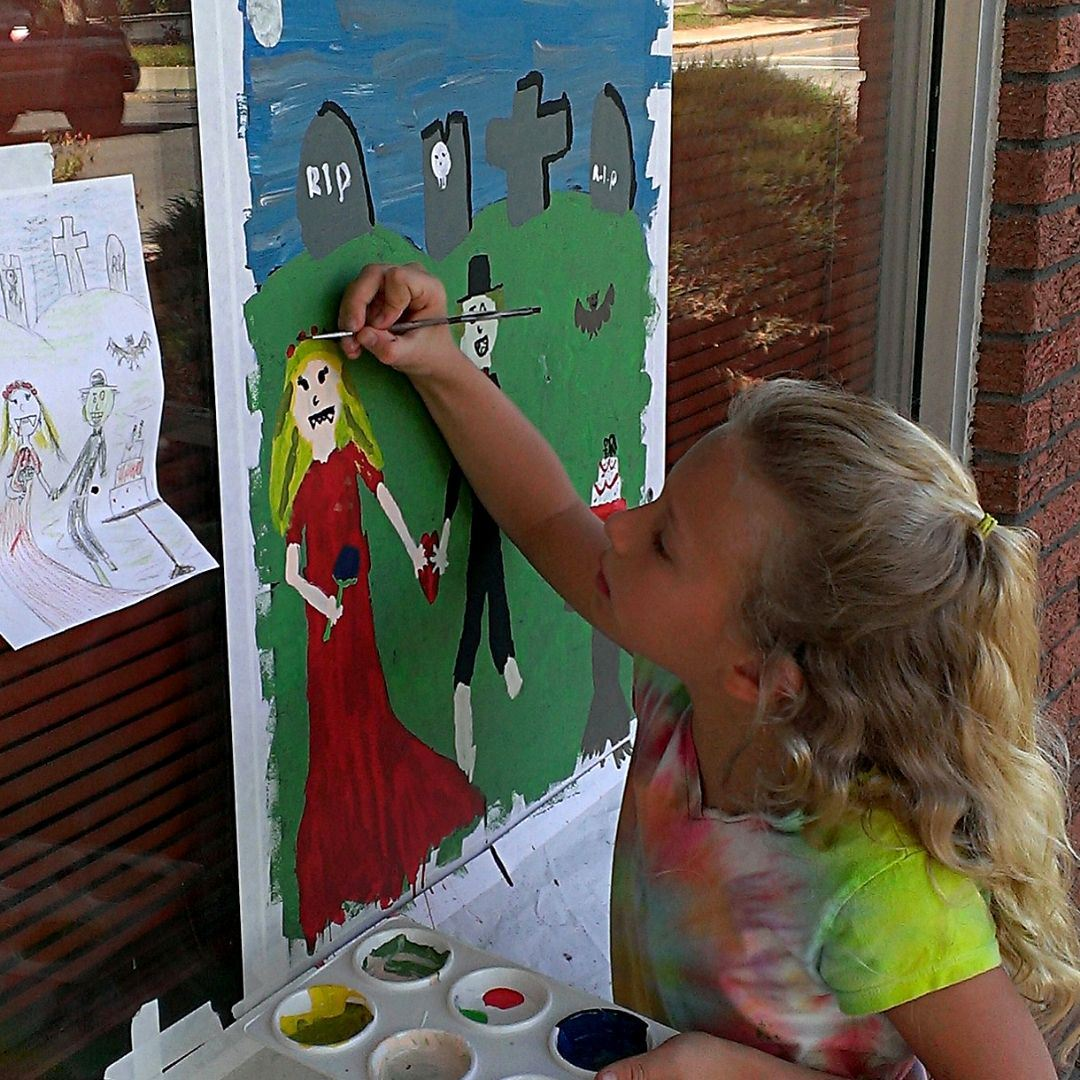Image of young girl painting on a window