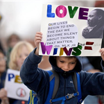 Image of young boy holding an MLK poster