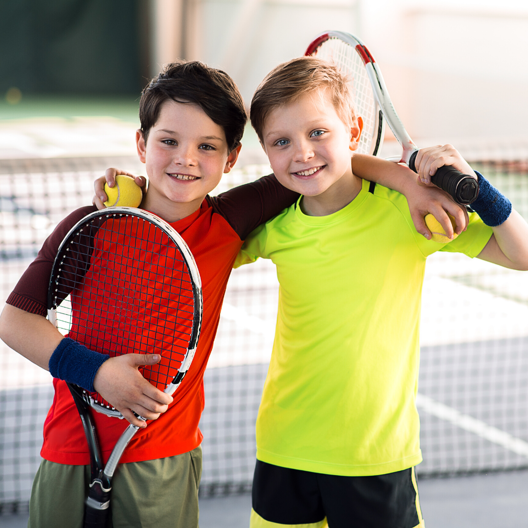 two young boys holding tennis racquets on a tennis court