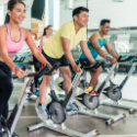 men and women in a cycle class