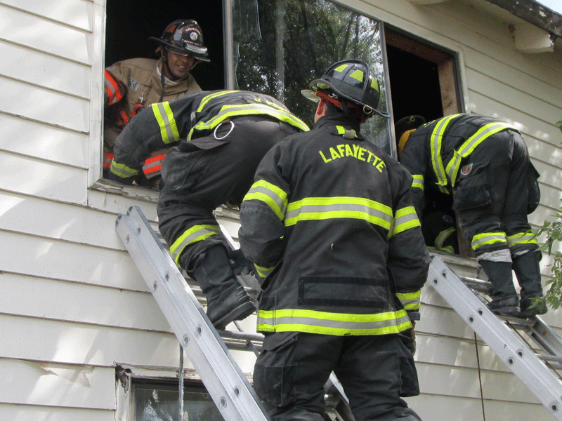 crew entering home through 2nd floor window