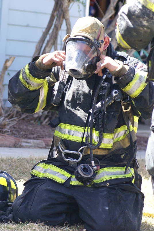 Fire Fighter taking off mask in rehab after extinguishing fire