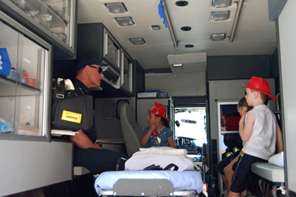 Lt. Dan Garrett doing a show and tell for 2 young boys in back of ambulance
