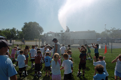 spraying water on kids at soccer camp to cool them using deck gun
