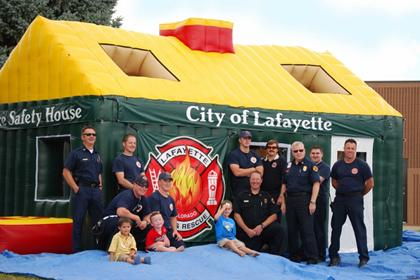 LFD Staff posing with 3 kids in front of the LFD Fire Safety House