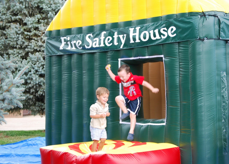 Kids jumping through the window of the LFD Fire Safety House