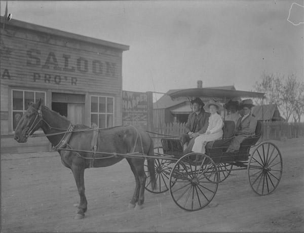 Horse and buggy with passengers on Public Road in front of a saloon