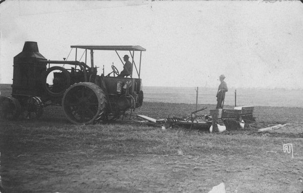 Two men and a tractor in a harvest field