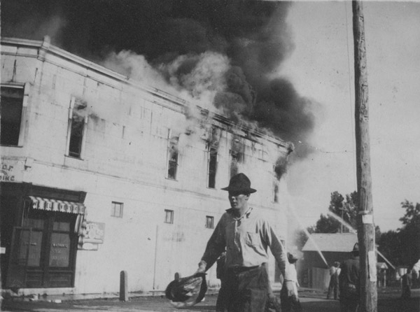 A man walks by the burning W. H. Frantz store building
