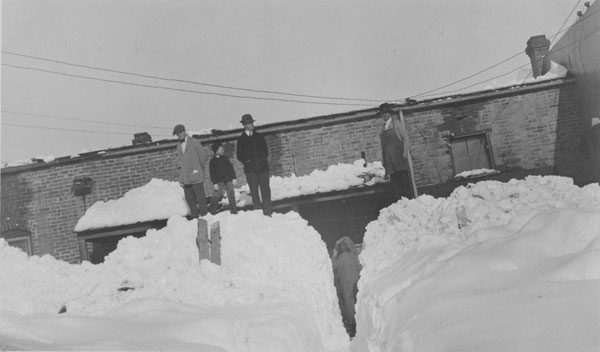 Three men and a boy standing on top of a snow drift behind a building