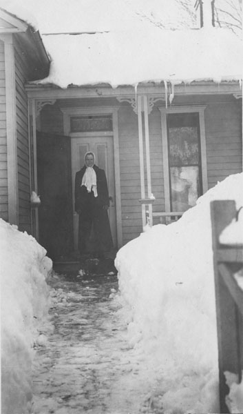 A woman standing on the front porch of a house in the snow