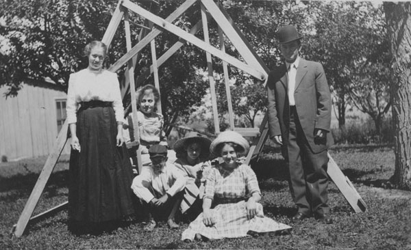 A group of people sitting on a wooden swing in a yard