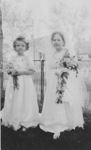 Two young girls dressed as a bride and bridesmaid