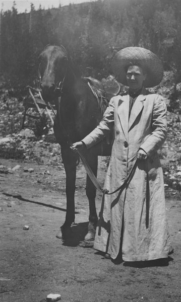 A woman wearing a riding outfit, standing next to a horse