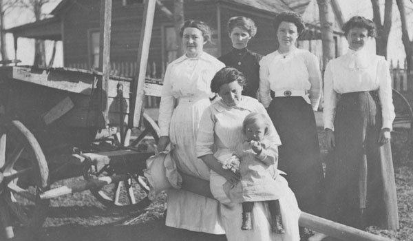 Five women and a baby next to a large wagon