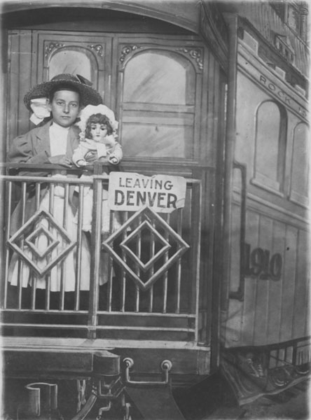 Ruth Gwinnup standing on a train with a doll