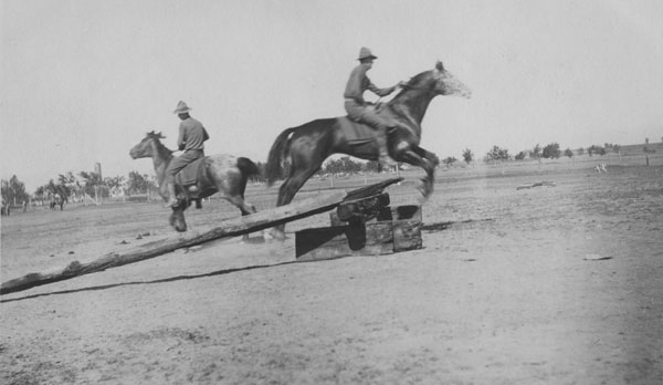 Soldier and horse jumping a hurdle