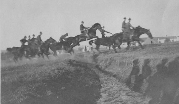 Army troops on horses, jumping over a culvert