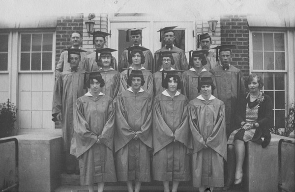 Graduating class of 1929 in caps in gowns, standing on the front steps of Lafayette High School