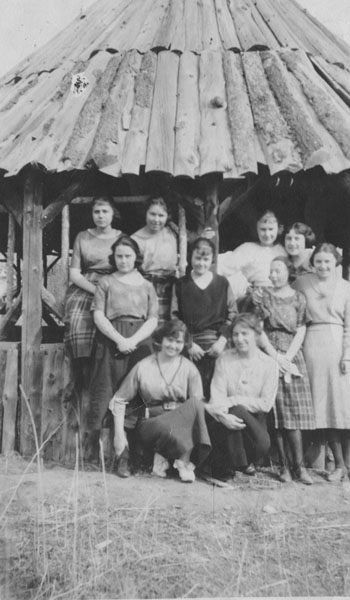Campfire Girls gathered in front of a log hut