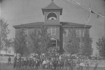 Students standing in front of first school building in Lafayette