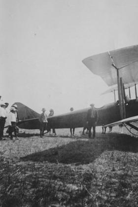 Biplane in field, side view
