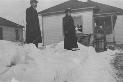 A man and a woman standing on snow in front of a house