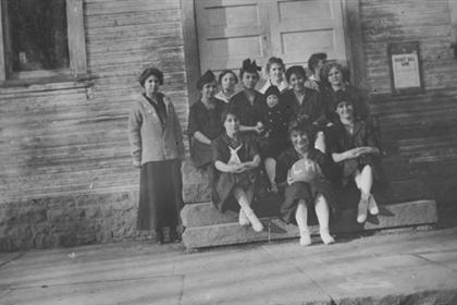 Lafayette High school girls basketball team sitting on the front steps of a building