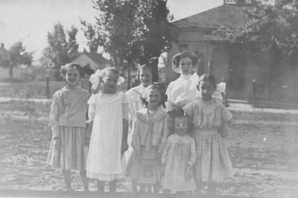 Group of seven young girls standing on a Lafayette street