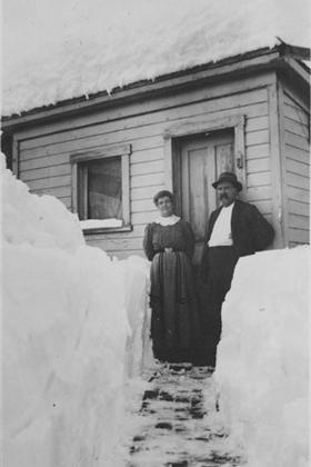 A woman and man stand outside a house in the snow