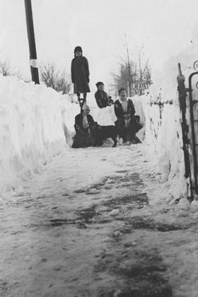 Three children, a woman and a dog sit in the snow on a sidewalk