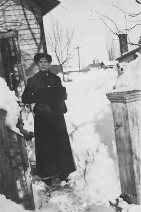 A woman with a muffler stands outside a house in the snow