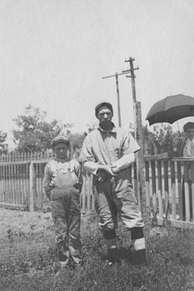 Baseball player and a boy standing in a yard