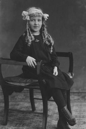 Formal portrait of girl seated.