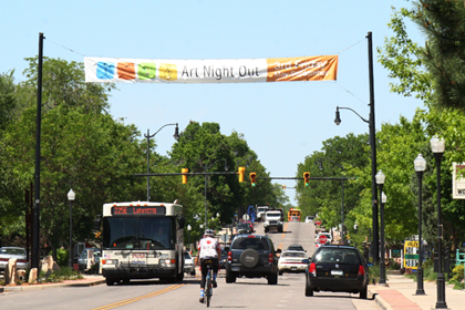 Street scene with a cyclist and RTD bus, and the Art Night Out banner over Public Road