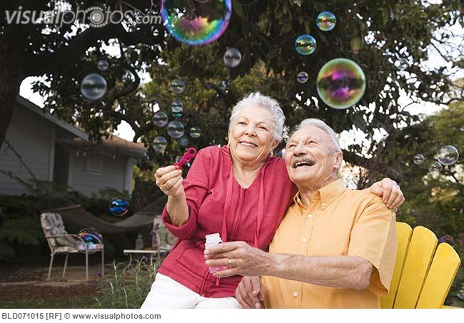 senior_couple_blowing_bubbles_outdoors_BLD071015.jpg